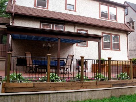 Wooden posts are combined with metal railings to create a decorative fence for a raised patio.