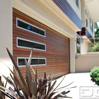Custom architectural contemporary garage door custom crafted in ipe wood in an asymmetrical window design with tinted glass and silver frame | Yelp