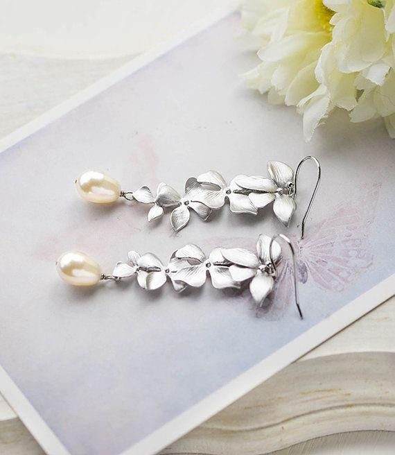 Bruids oorbellen. Zilveren bloem van orchideeën en lange bengelen oorbellen van Swarovski crème Teardrop parels. Bruiloft oorbellen, bruidsmeisjes sieraden.  Mooie trapsgewijze orchideeën in mat zilveren afwerking worden gecombineerd met Swarovski crème teardrop glas parels. De orchideeën zijn verbonden met rhodium plated over messing Franse haak oor draden. Parels zijn verkrijgbaar in verschillende kleuren en kunnen worden aangepast op uw verzoek.  Totale lengte: ca. 2 1/2(65mm)  Swarov...