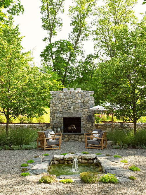 Outdoor fireplace integrated into wall. Gravel path and sitting area with teak seating. Nice bubbling water feature.