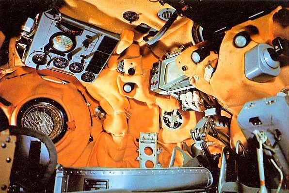 Interior de la nave soviética Vosjod 1 (1964). Obsérvese que a pesar de tratarse de una versión externamente casi idéntica en cotas a sus predecesoras Vostok, las Vosjod disponían de suficiente espacio para alojar a tres cosmonautas al haberse suprimido los asientos eyectables en caso de emergencia en el despegue. Toda una prueba de confianza de los soviéticos en la fiabilidad de sus lanzadores