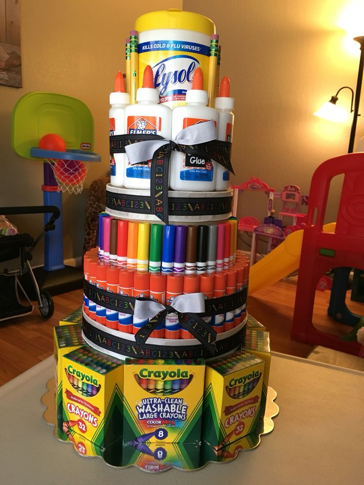 School supply cake for Teacher  Appreciation week or end of the year gift. One container of disinfecting wipes, 7 4oz glue bottles, 6 pencils, 4 boxes of 10 count markers, 34 glue sticks, 1 8 count box of large crayons, 9 boxes of 32 count crayons. Ribbon of your choice. I used 2 brown paper crafting boxes. 1 10.5 inch for the bottom base and then one smaller one for the middle part. I don't remember the size.