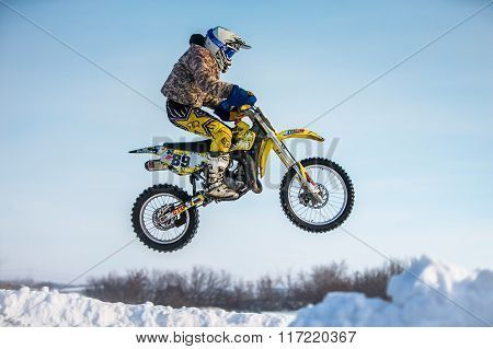 closeup rider on a motorcycle jump on mountain. background blue sky