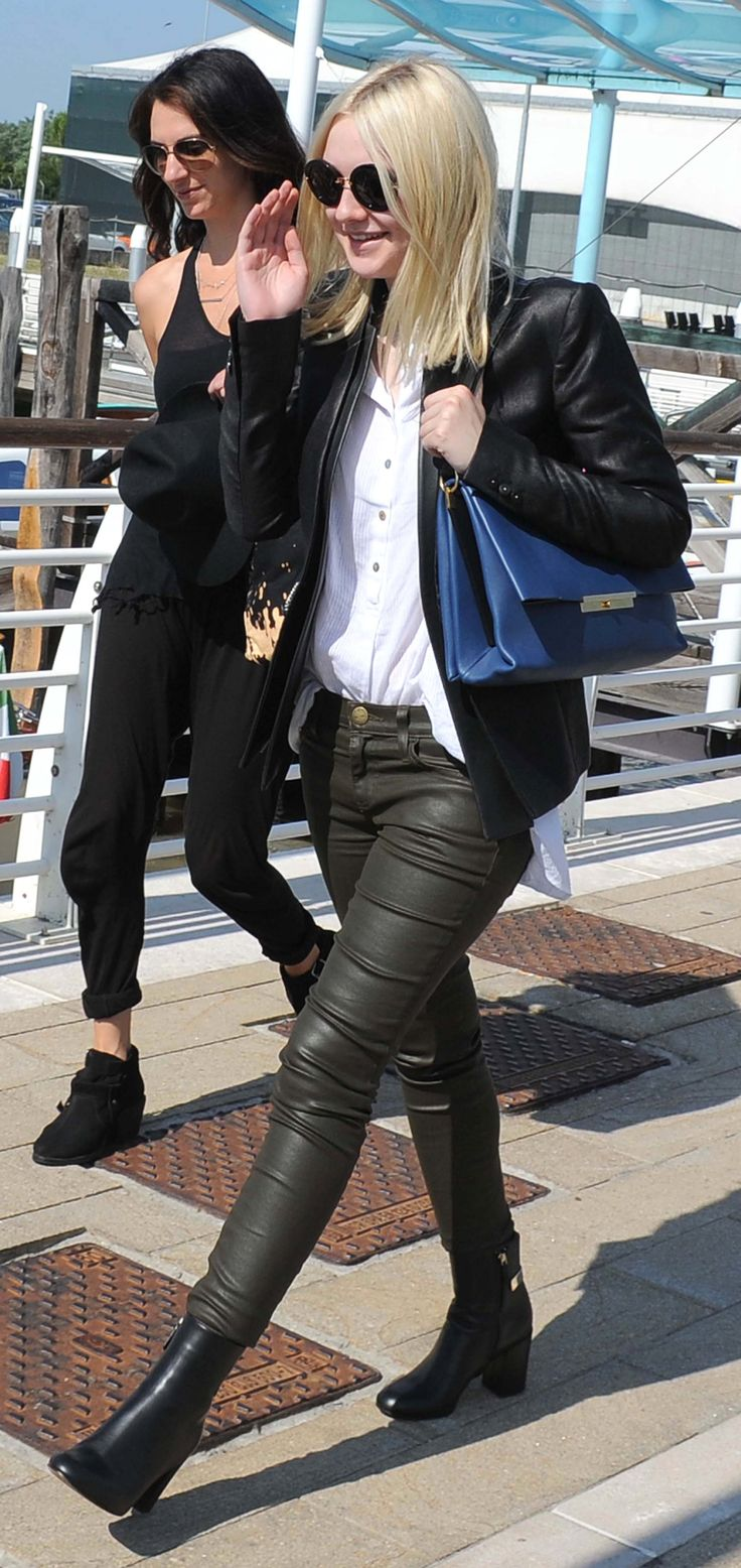 Opting for a more mature look while in Venice to promote her new movie, Night Moves, Dakota wore a dark-hued ensemble consisting of a white polo shirt, green leather pants from Current / Elliott, black booties, and a black leather jacket.