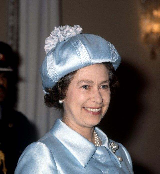 """Shown in 1979 in the hat that shares a name with her grand Scottish countryside estate—Balmoral Castle, in Aberdeenshire—the Queen wears her own interpretation of a traditional """"Balmoral hat,"""" rendered in icy blue satin with a silk pouf rather than the traditional felted wool."""