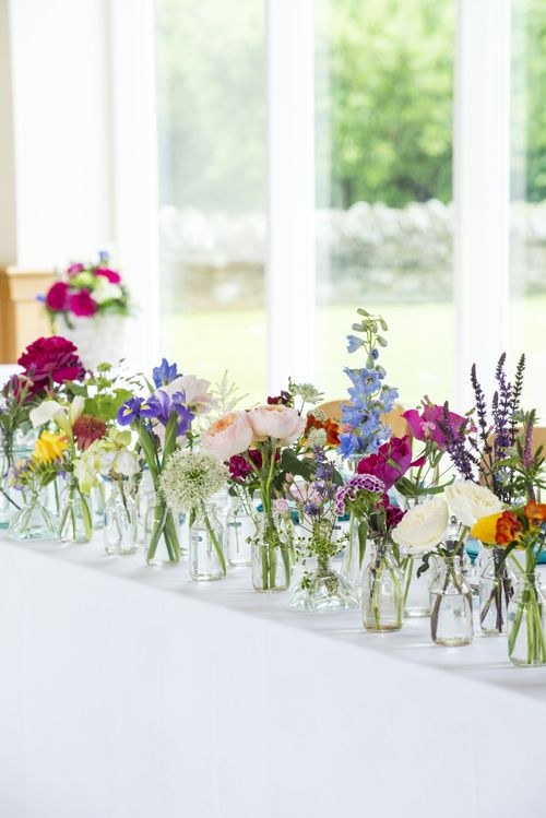 Single blooms in bottles massed together - roses, alliums, delphiniums, irises, freesias and other flowers.
