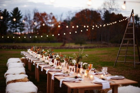 Evening fall harvest dinner with hand-tied herb bundles and hay bales + sheepskins as seating.