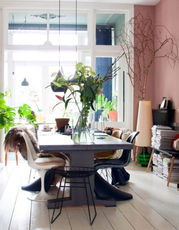 dining room with pink walls and vintage vases with green plants and branches. / sfgirlbybay