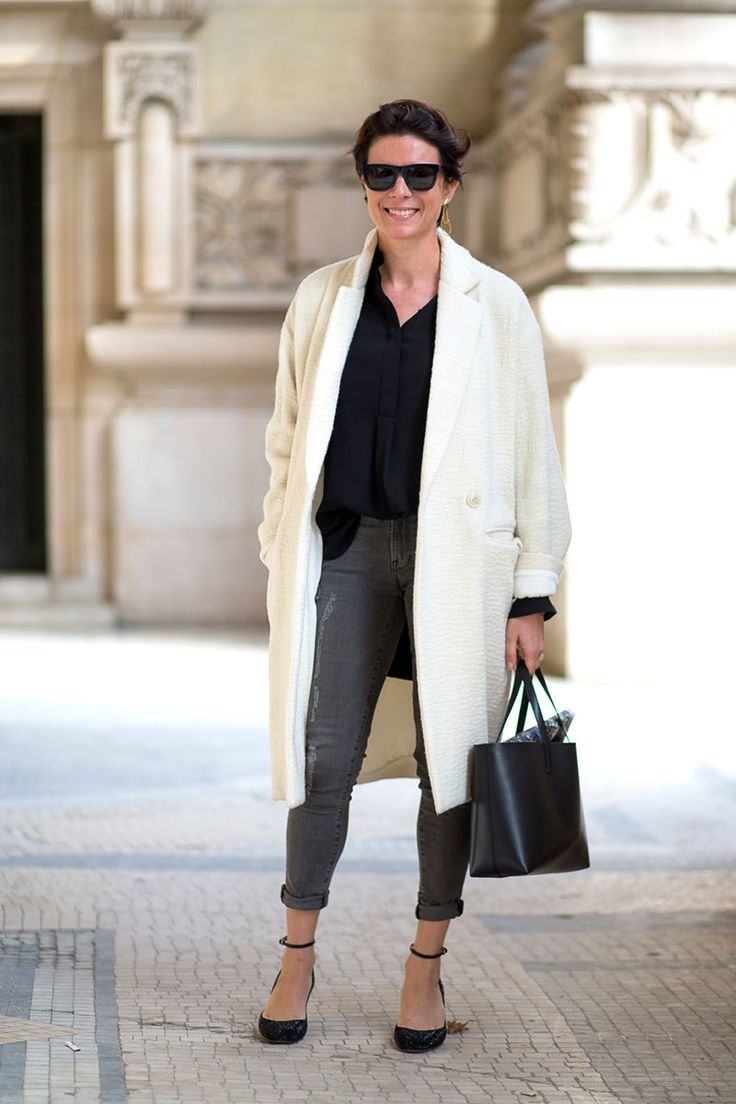 White cocoon coat, black blouse and gray jeans.
