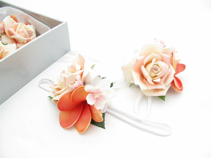 Wristlets with a coral frangipani, cherry blossom and blush Classic Roses. Find your perfect wedding flowers at http://www.loveflowers.com.au