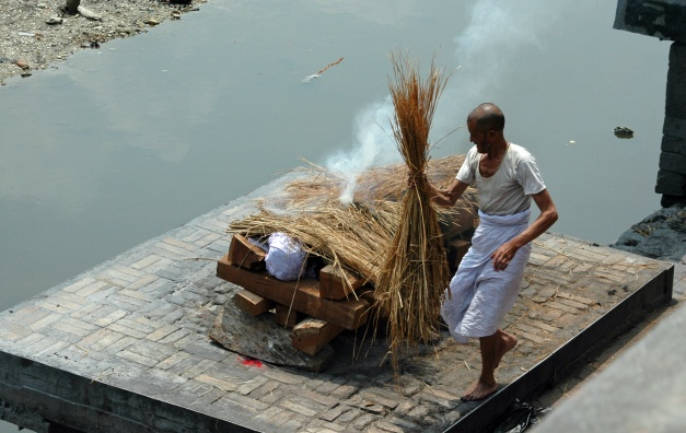 Gentleman from the Dom caste prepares a funeral pyre for a Hindu cremation at the Arya Ghats in Pashupatinath, Nepal