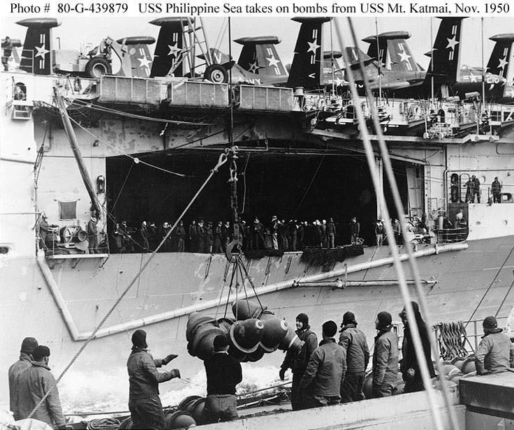 """USS PHILIPPINE SEA CV-47. Receives bombs from USSMount Katmai (AE-16) during underway replenishment off Korea, 29 November 1950. Note crewmen standing in the carrier's forward hangar bay, and Grumman F9F-2 """"Panther"""" fighters and LeTourneau crane parked on her flight deck. 