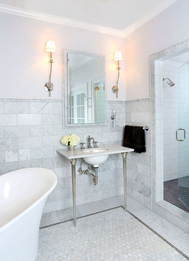 This bathroom is the ultimate spa-like retreat with Carrera marble tile, a  French