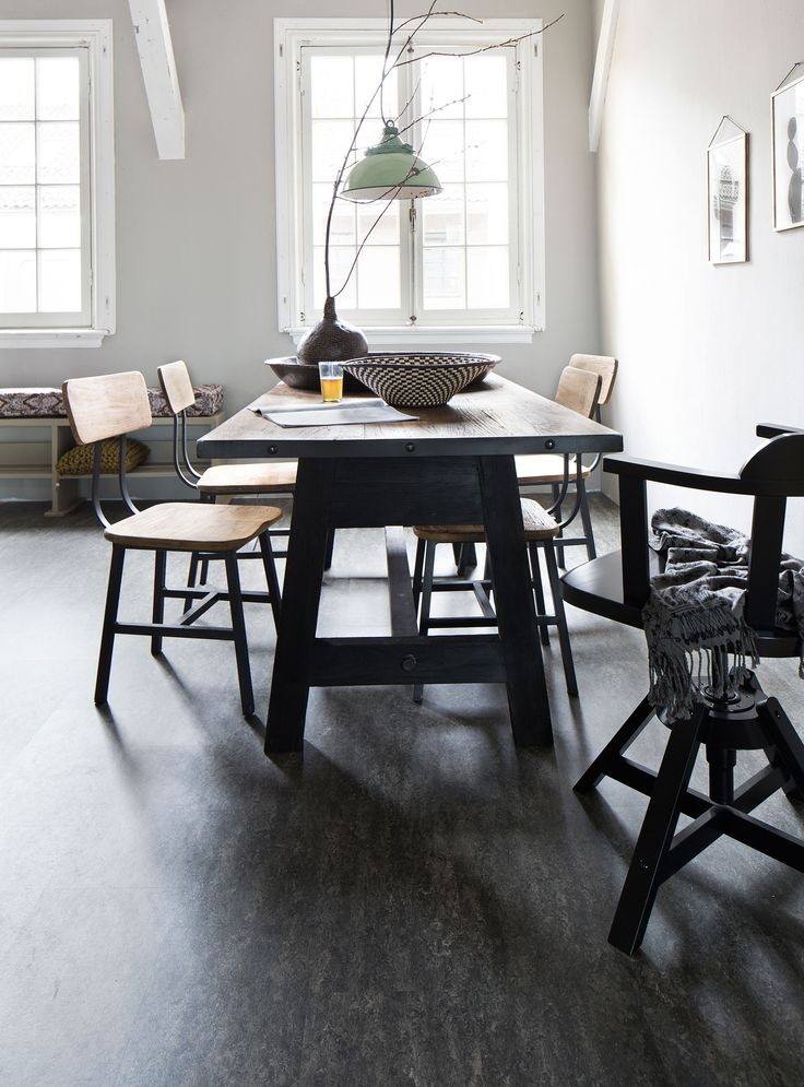 Dark marmoleum floor with wooden dining table and chairs. On the wall are posters and on the table a vase and a basket as an accessory.| Photographer Alexander van Berge, Jansje Klazinga, Anna de Leeuw | Styling Fietje Bruijn, Marianne Luning, Frans Uyterlinde | vtwonen catalog autumn 2015 | #vtwonencollectie
