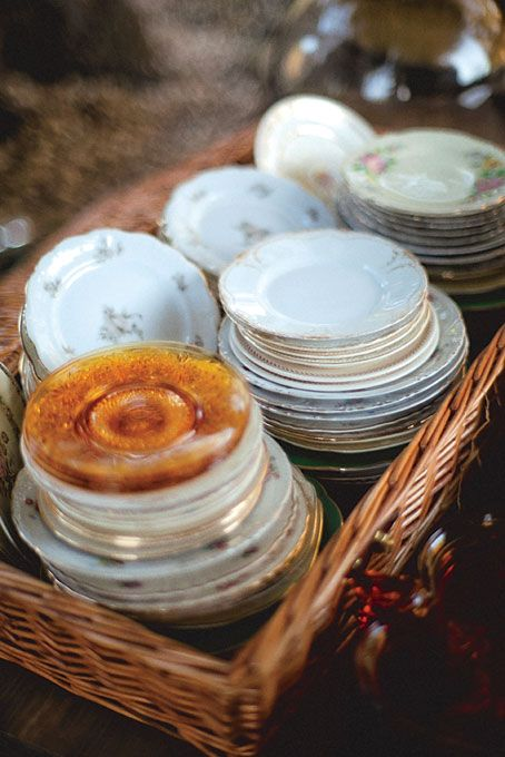 Vintage dinner plates at a rustic wedding reception. Each table had a picnic basket in the center where guests grabbed their plates and cutlery.