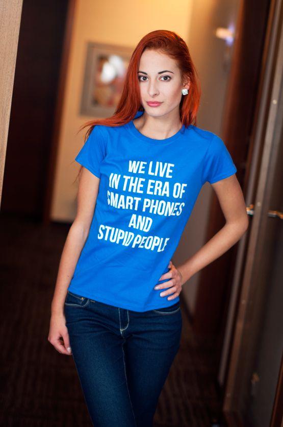 """T-shirt We Live in the Era of Smart Phones De vrouwelijke versie van de klassiker is een nauwsluitend model met verkorte mouwtjes en heeft een opdruk met de grappige tekst: """"We Live in the Era of Smart Phones and Stupid People"""". Blikdicht met aangenaam hoge stofdichtheid en een eersteklas verwerking."""