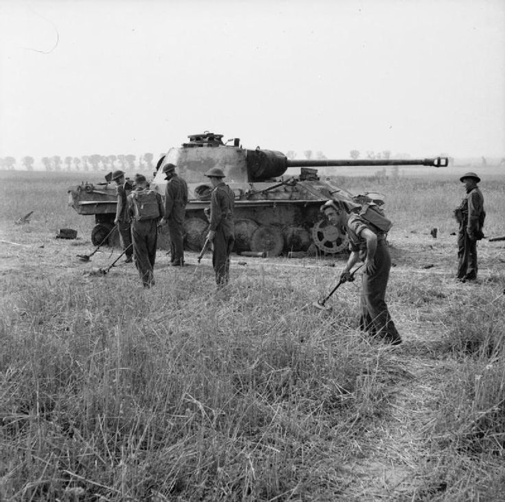 British Royal Engineers search for mines near a knocked out German Panther tank, near Villers Bocage, 4 August 1944.