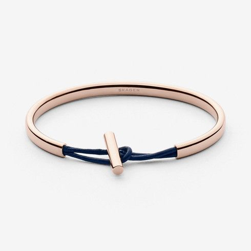 This rose-gold-tone steel bracelet has navy leather detailing at the closure.