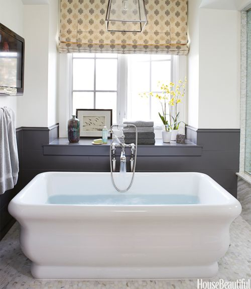 The Michelangelo soaking tub from Hydro Systems takes center stage in the master bath of a comfortable bachelor pad in Southern California designed by Parrish Chilcoat and Joe Lucas. Ballard Designs lantern.   - HouseBeautiful.com