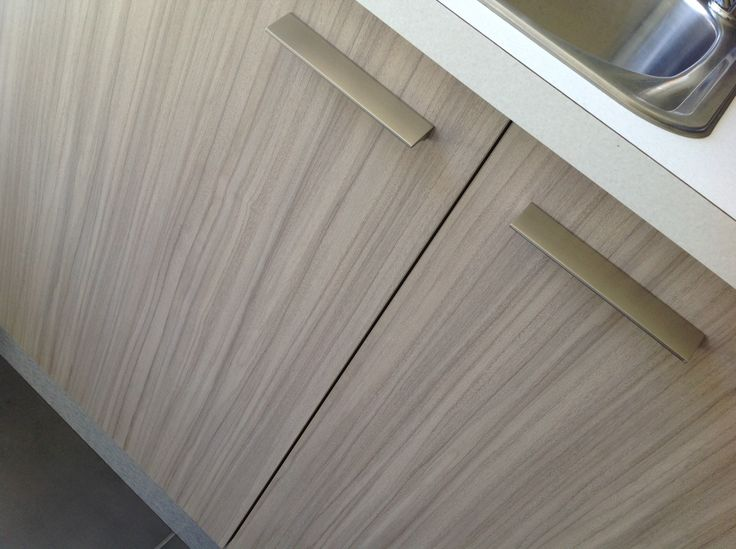 """Laundry - Our Colour Consultant chose for the cabinetry, Laminex Impressions in the Riven Finish """"Avignon Walnut."""" (vertical grain) For the bench top, our Colour Consultant chose the Spark Finish """"Fresh Snow."""""""