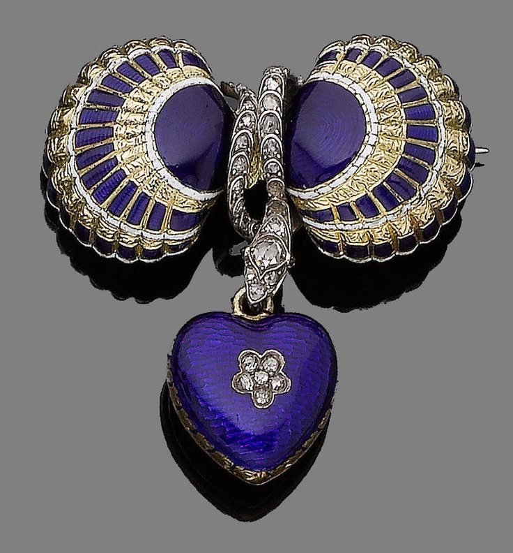 A mid 19th century enamel and diamond locket brooch. The two engraved scallop shells with applied royal blue guilloché and white enamel, separated by a rose-cut diamond serpent with cabochon garnet eyes, suspending a similarly-set heart locket with inlaid rose-cut diamonds, with a glazed compartment to the reverse.