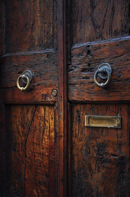 Old wooden double doors with brass handles.