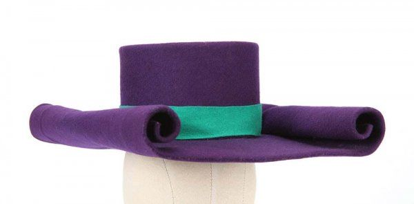 "Meinhardt Raabe ""Munchkin Coroner"" screen-worn hat from The Wizard of Oz. (MGM, 1939) This Adrian-designed screen worn hat is constructed of purple felt featuring a green headband. The square brim has distinctive rolled edges; a blue ribbon, which was worn behind the ears, hangs down from the hat. Brim is 15 in. long and the headpiece stands 4 in. tall with a 7 in. diameter (slightly oval)."