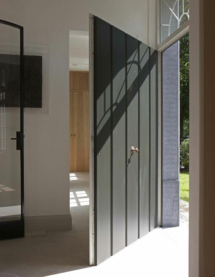 contemporary country elements - panelled front door in charcoal grey clean white interior, modern oak and metal framed door Villabouw Vlassak Verhulst: