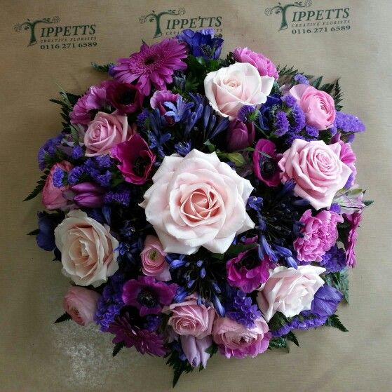 Pink and purple posy arrangement of flowers including  roses.