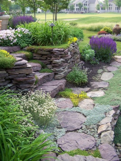Stone wall in the garden, The dry stack stone wall surrounds an elevated patio. I matched the stone to the house so the house looked like it grew out of the ground. There are large center stairs, a small set of stairs on one side, and a stone path ramp on the other side., Side steps with the path leading up to them., Gardens Design