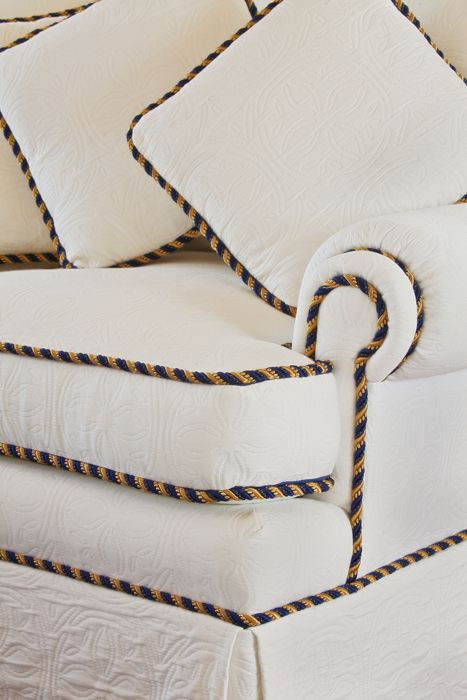 Elegant gold and blue trim adds elegance to the white-on-white sand dollar upholstery.