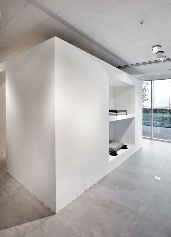 Large wall with build-in, deep shelves inside the Royal Mosa architectural showroom in Amsterdam by 3d communication office Zeeprojects.
