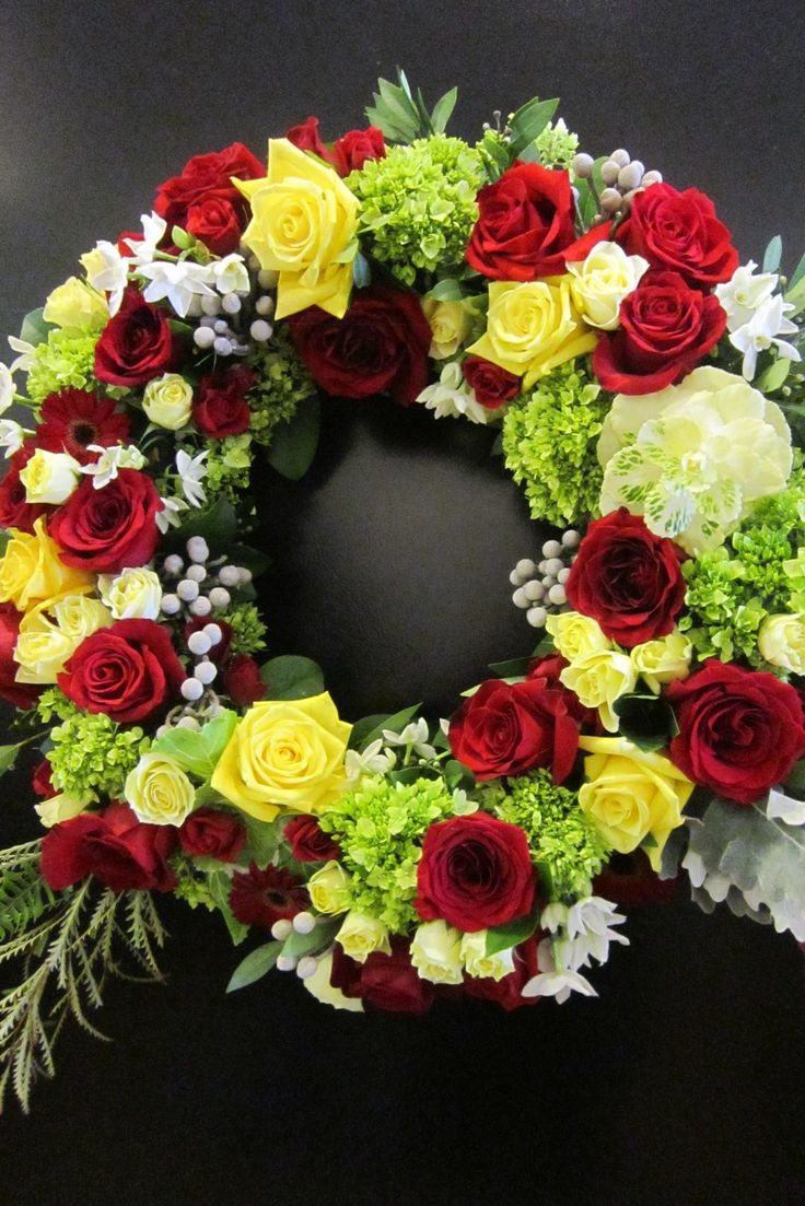 Standing wreath of red and yellow roses with green hydrangea.