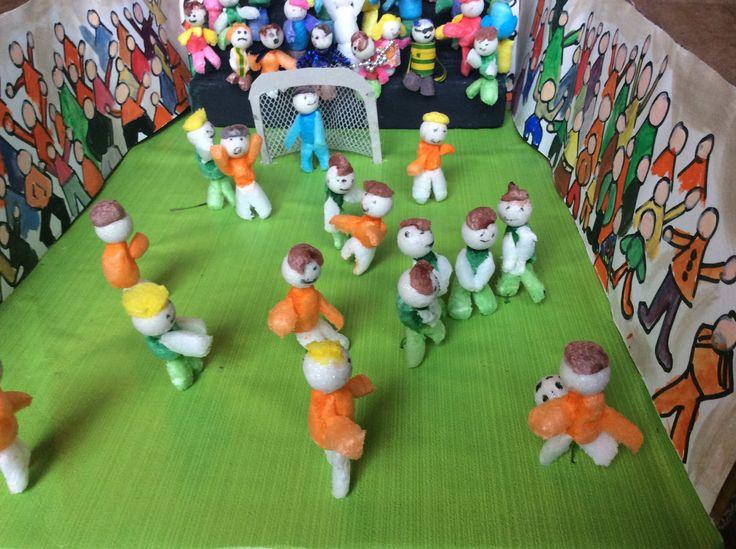 Voetbalelftal en voetbalstadion. Surprise gemaakt van pepschuim, kerstdecoratie als hoofdjes. Tribune van oase gesneden. Fruitdoos als ondergrond