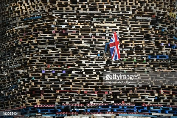 A Loyalist youth climbs a large bonfire construct in preparation for their 11th night bonfire at the New Mossley estate on July 9, 2015 in Belfast, Northern Ireland. The New Mossley bonfire is considered by many to be the biggest in the province this year.
