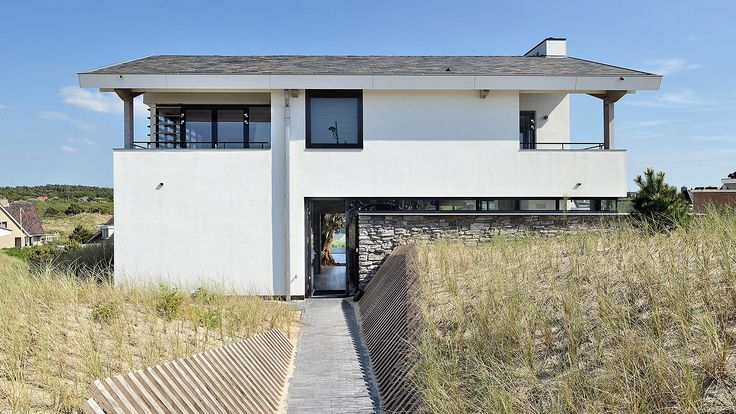 Dune villa in Bergen aan Zee. Thanks to the stone wall, the house blends in perfectly in the surrounding dune area. Design by BNLA architects, photography by Studio de Nooyer.
