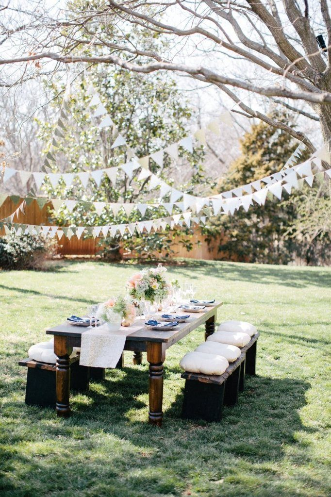 Lovely open space, beautiful garden party wedding style / backyard. Garland in trees, table reception outdoor.