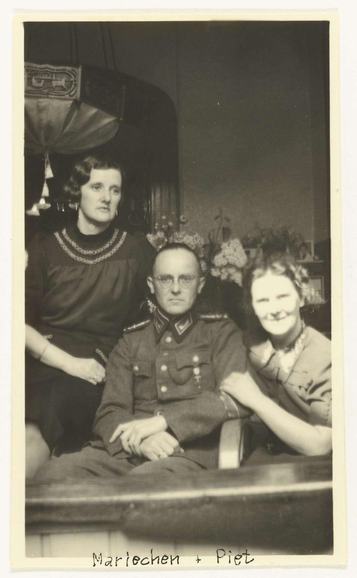 Anonymous | Wehrmacht soldaat met twee Nederlandse vrouwen, Anonymous, 1940 - 1941 | Een oudere en een jongere Nederlandse vrouw poseren met een Duitse militair in een kamer. Op de voorkant staat: Mariechen en Piet.