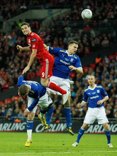 Andy Carroll of Liverpool outjumps Aron Gunnarsson and Ben Turner of Cardiff City during the Carling Cup Final match between Liverpool and Cardiff City at Wembley Stadium on February 26, 2012 in London, England.