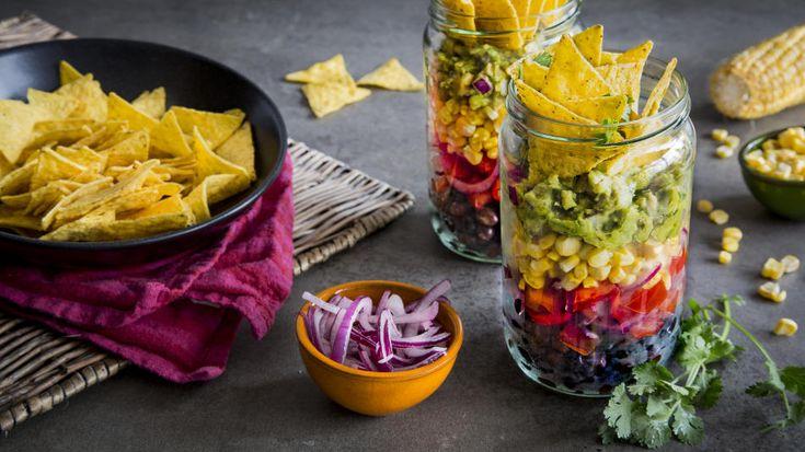 Salat im Glas aus Bohnen, Mais, Salat, Salsa, Guacamole und mit Taco-Chips-Topping.