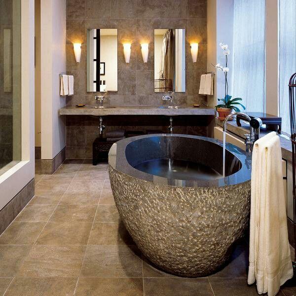 Oval bathtub by stone forest Een stenen badkuip van graniet, met gepolijste binnenkant en een ruwe buitenkant.