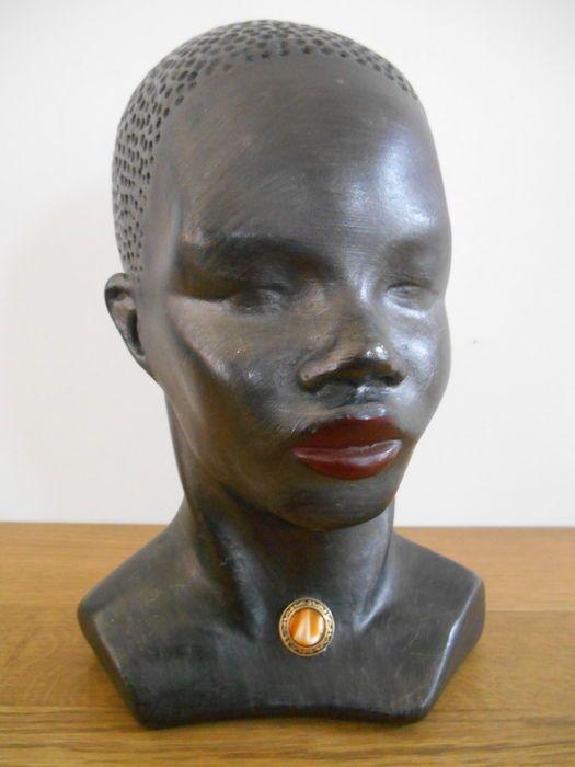 Opmerkelijke buste van een Afrikaanse vrouw uit ca. 1950. Vrouw heeft mooi juweel aan haar hals. Beeld is gemaakt van een soort gips en is zeer mooi gedetailleerd. Opmerkelijk is dat de lippen van de vrouw mooi rood gekleurd zijn. Op de achterkant van het beeld staat iets gegraveerd (moeilijk leesbaar: vermoedelijk nr. 2). Naam van ontwerper is nergens terug te vinden.  Afmetingen: 24 cm hoog en 16 cm breed (diepte is 17 cm).  Beeld is nog in zeer goede staat (geen beschadigingen --> zie ...