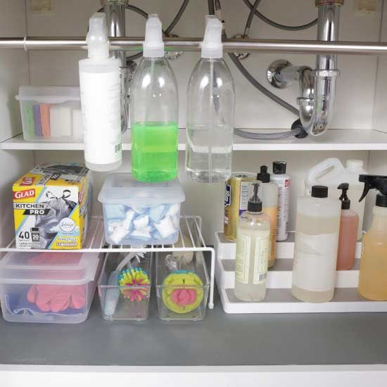Freshen up the cabinet under the sink with some quick and easy storage solutions. Line the bottom of the cabinet with pretty contact paper. Use clear containers to hold cleaning supplies like sponges, brushes, and dishwasher tablets. Add a tension rod to hang bottles and sprays.