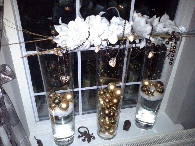 Hoge Glas vazen met water vullen poedersneeuw er op doen dan kerstballen eropleggen, en de bloemen boven op de vazen zijn foam bloemen lichtjes en kralenketting er door en klaar is kees, blij met de Action en Woonwinkel Entree in Yde