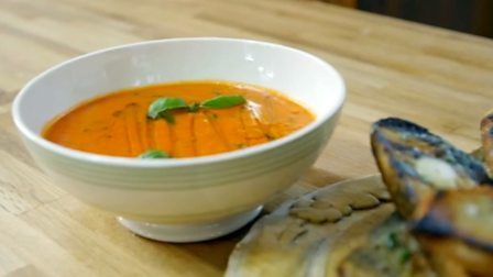 Roasted garlic and top-quality tinned tomatoes make all the difference to this simple soup. To simplify the garlic bread, just mix the roasted garlic with softened butter.  Equipment and preparation: you will need a free-standing mixer, clean sheet of muslin and stick-blender or food processor.