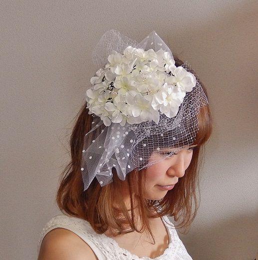 ヘッドドレス(クリップ式)前回即完売のアジサイのヘッドドレスが新しくなって登場です。 ホワイトのアジサイがぎっしりのトーク帽に、より繊細な印象になるよう かすみ草をポイントでプラスしました。 お花は1つ1つ手でつけて、丁寧にお作りしております。ドットのチュールとネットのチュールがウェディング気分を盛り上げます。 (チュールは取り外し可能です。)大きすぎず小さすぎず、上品なドレススタイルに... オシャレな花嫁様につけて頂きたい1点です。