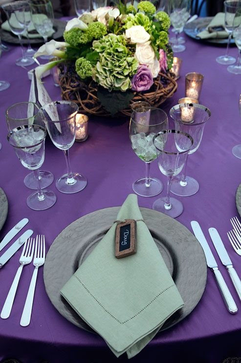 Green napkins and arrangements of green hydrangeas and white and purple roses in woven baskets top purple tables.
