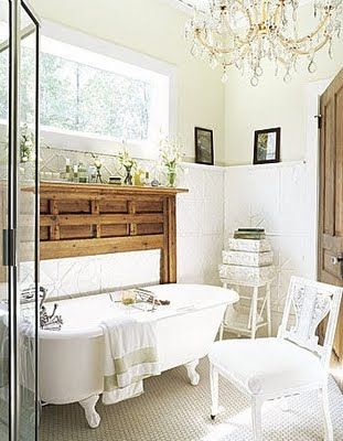 Reclaimed vintage fireplace mantle over the tub for shelving. Functional and beautiful. Also, love the chandelier in here!