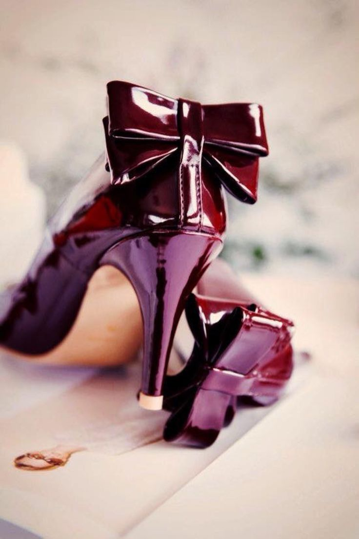 Patent leather wine-colored dress shoes with bows at the heels