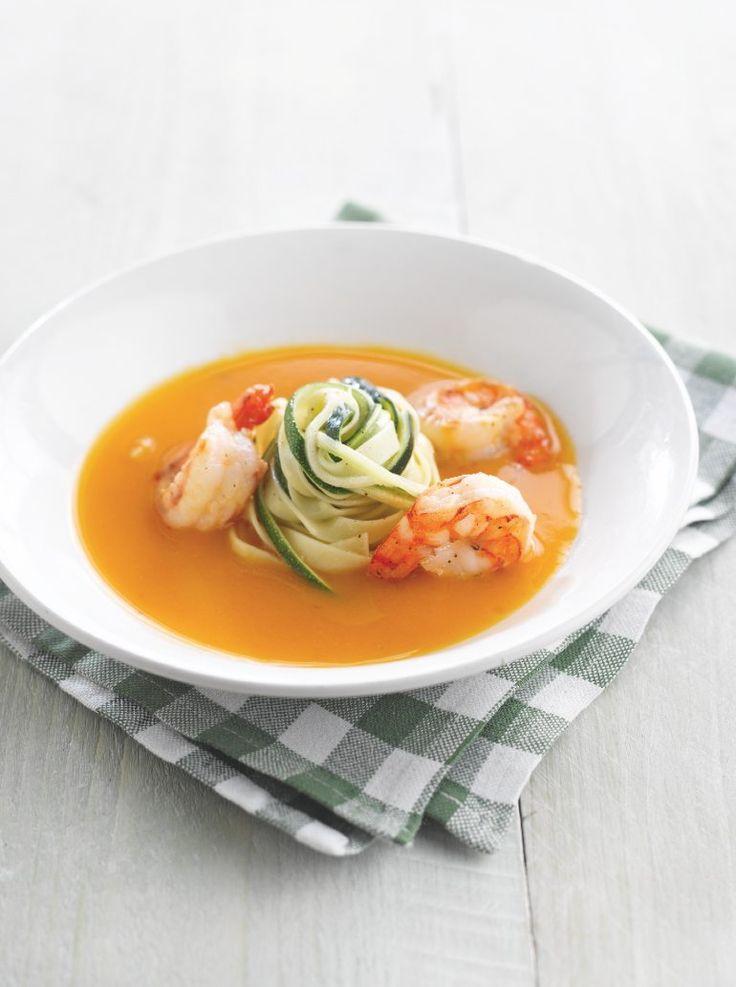 Pompoensoep met tagliatelle van courgette en scampi's  bereiden: Snij de pompoen, ui en look fijn. Stoof in 2 cl olijfolie. Strooi er de bloem over en meng door elkaar. Voeg de gevogeltebouillon toe. Laat zachtjes koken onder een deksel. Mix na 30 minuten koken. Kruid met peper van de molen en zout. Trek smalle repen van de courgette en stoof ze kort in de gesmolten boter.